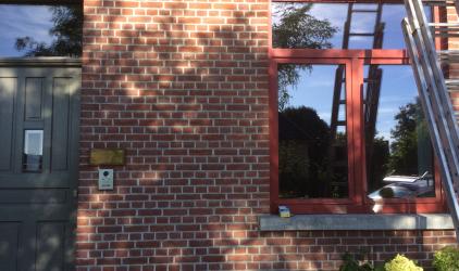 bruine gevel met rode alu ramen